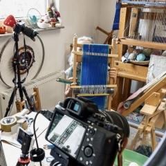 Das Foto zeigt den Blick in das Webstudio von Ingrid Frank, die einen kleinen Webrahmen in der Hand hält, der mit blauem und grünem Garn bespannt ist. Im Vordergrund und an der Seite sind die Kameras sichtbar, mit denen der Kurs online übertragen wurde. Im Hintergrund ist ein Teil eines sehr großen Webstuhls sichtbar auf dem ein Teil eines in Arbeit befindlichen Teppichs in weißer Wolle zu sehen ist.